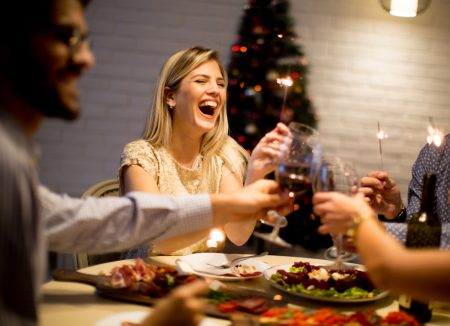 Young people celebrating New Year and drinking red wine